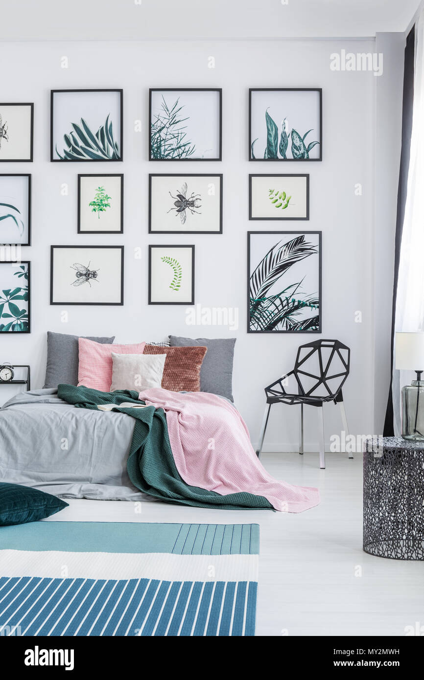 Real Photo Of A Wide Bed Standing Next To A Black Chair In A Bedroom  Interior With Plants Posters On A Wall And Rugs On A Floor