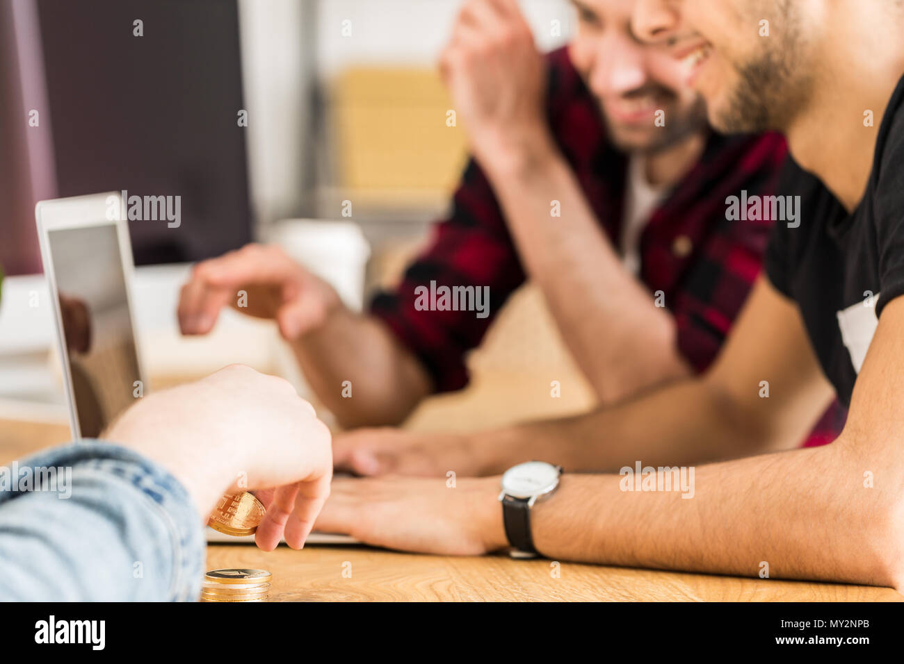 Group of happy friends sitting together in front of a laptop. Focus on man's hands holding cryptocurrency. Stock Photo