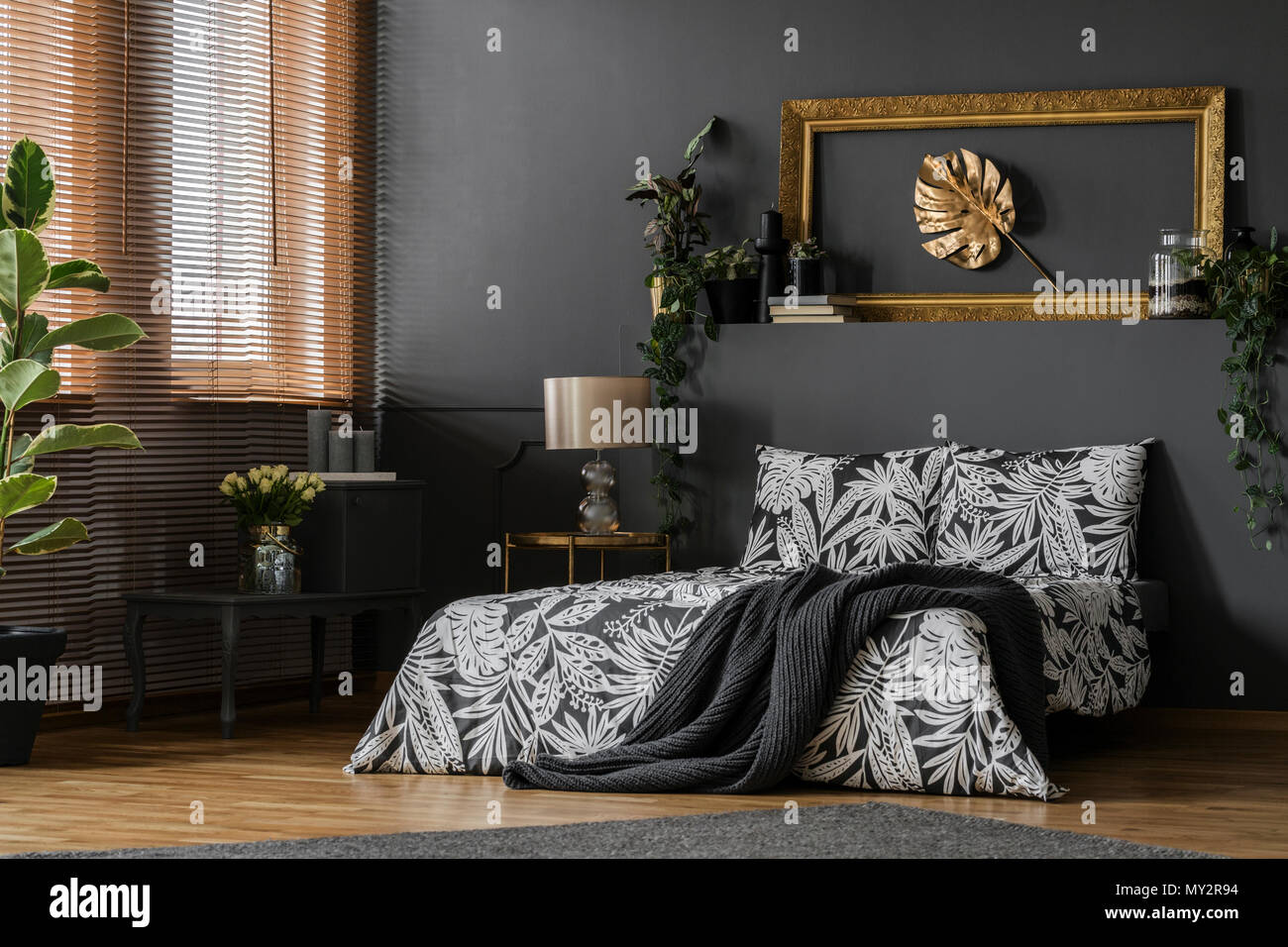 Glass Lamp Placed On A Gold End Table Standing By The King Size Bed In Dark Grey Bedroom Interior With Windows And Green Plants Stock Photo Alamy