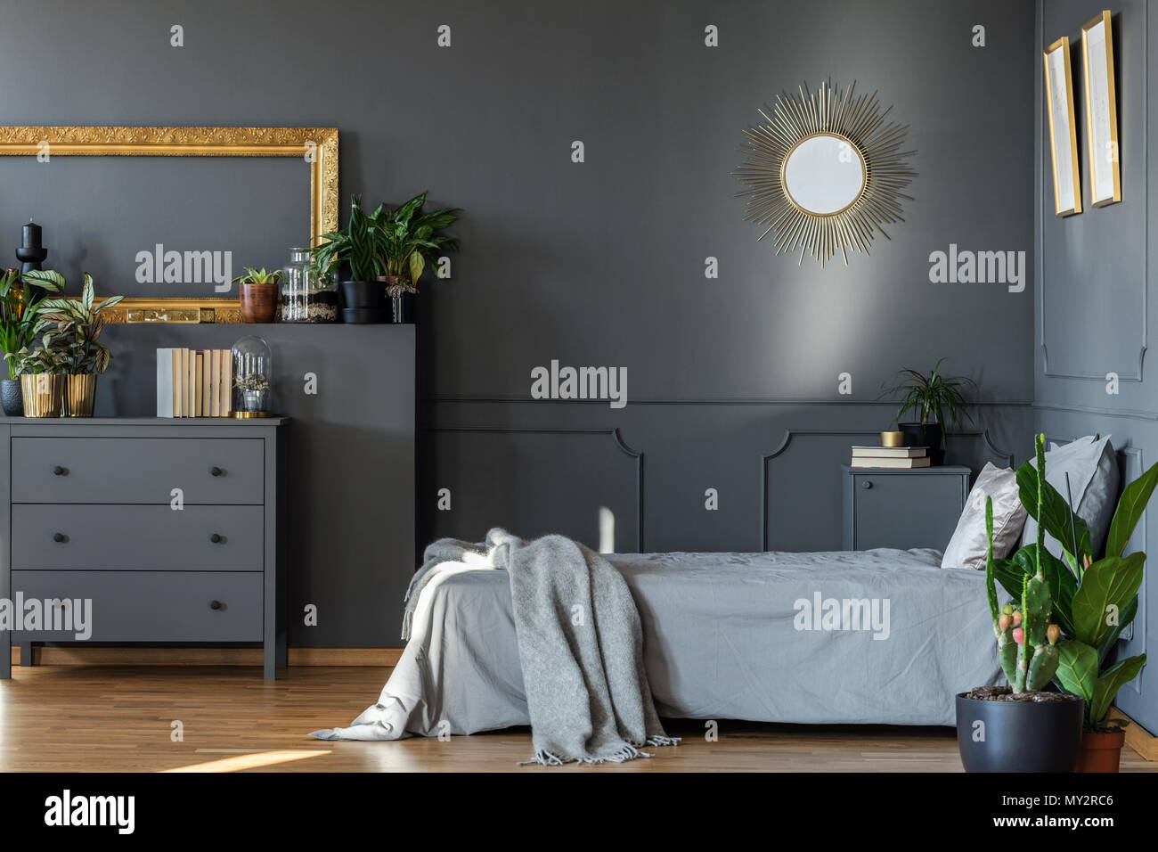 Decorative Mirror Hanging On The Wall In Dark Grey Bedroom Interior With Fresh Plants And Books On Wooden Cupboard Stock Photo Alamy
