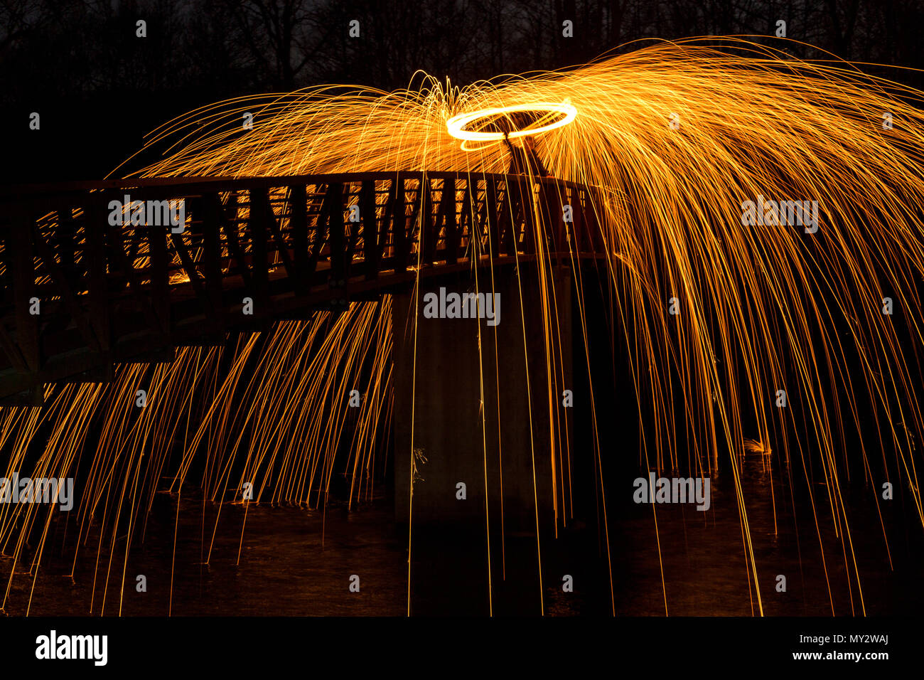 Light painting at night whirling steel wool burning at the end of a rope. - Stock Image