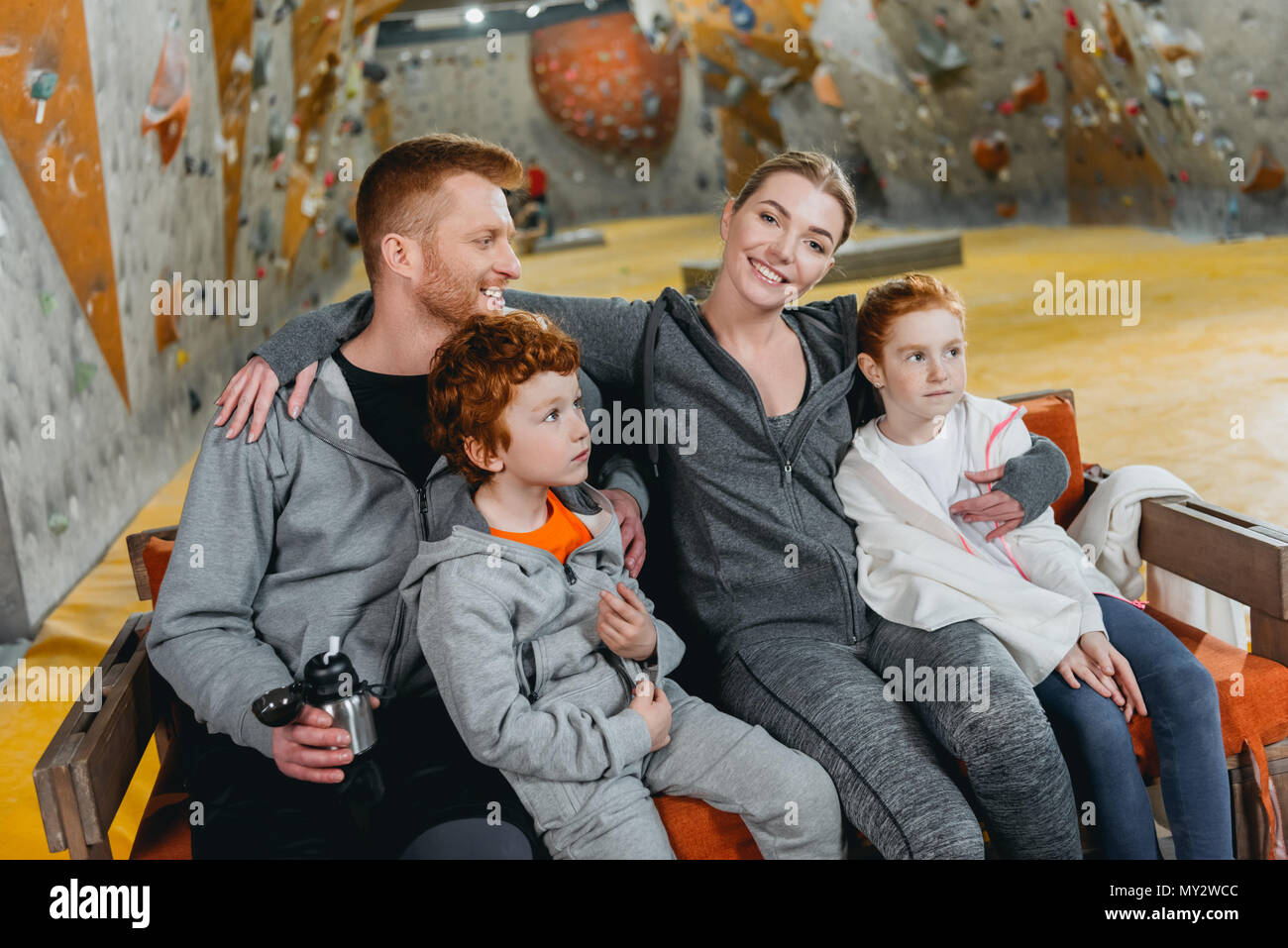 A family with kids at gym, sitting and relaxing on a bench, with climbing walls in the background - Stock Image