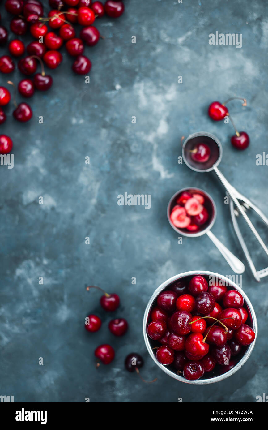Fresh cherries on a concrete background with a small metal bucket and an ice cream spoon. Making summer dessert concept flat lay with copy space. - Stock Image