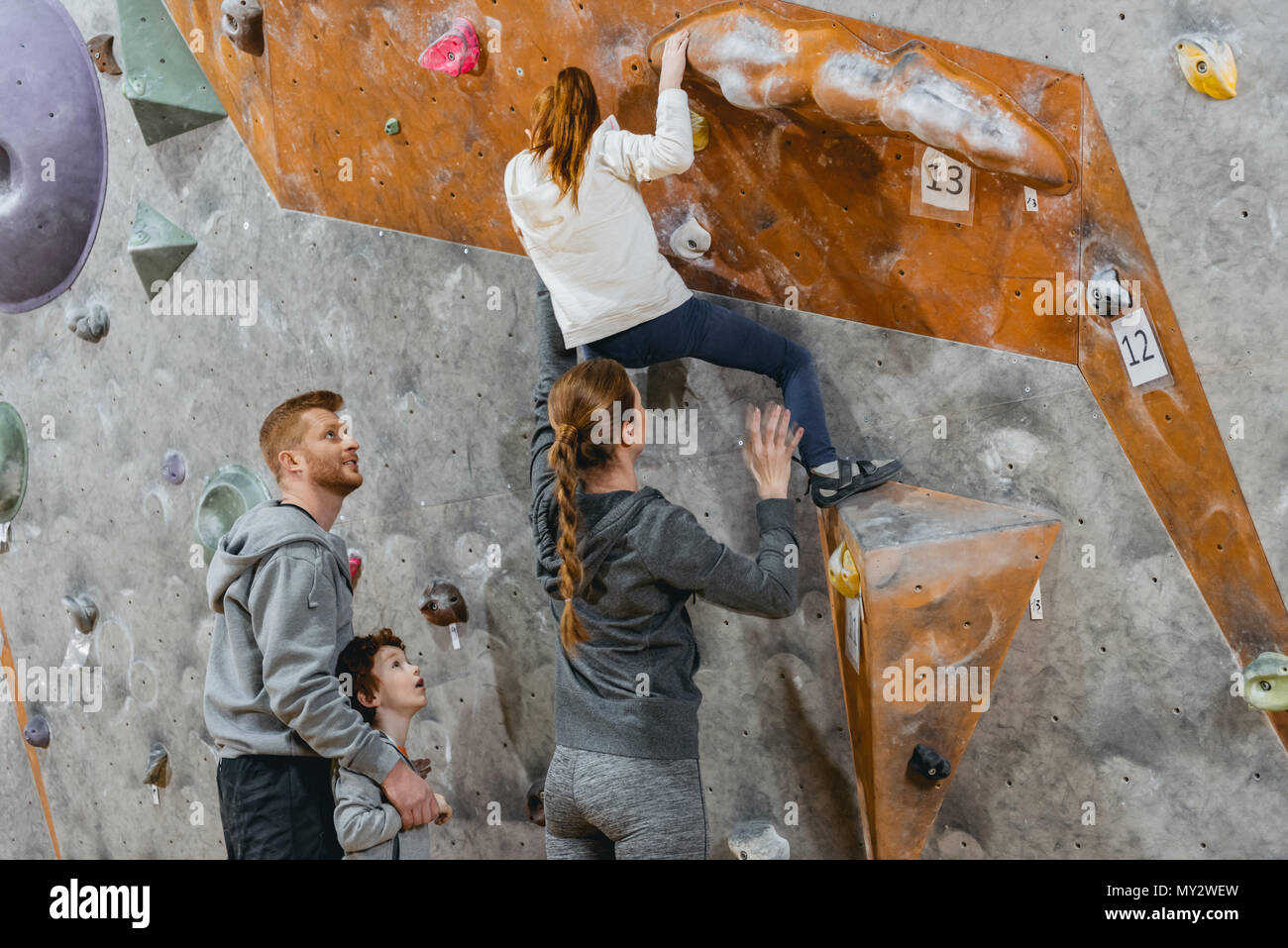 Little girl climbing a wall with grips and her mom supporting her from the back - Stock Image