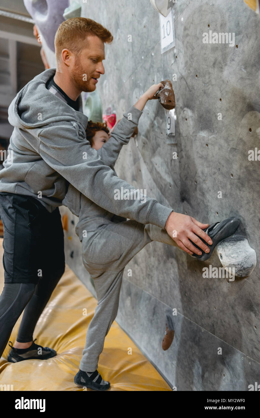 Full-length shot of young dad teaching his little son how to climb a wall with grips - Stock Image