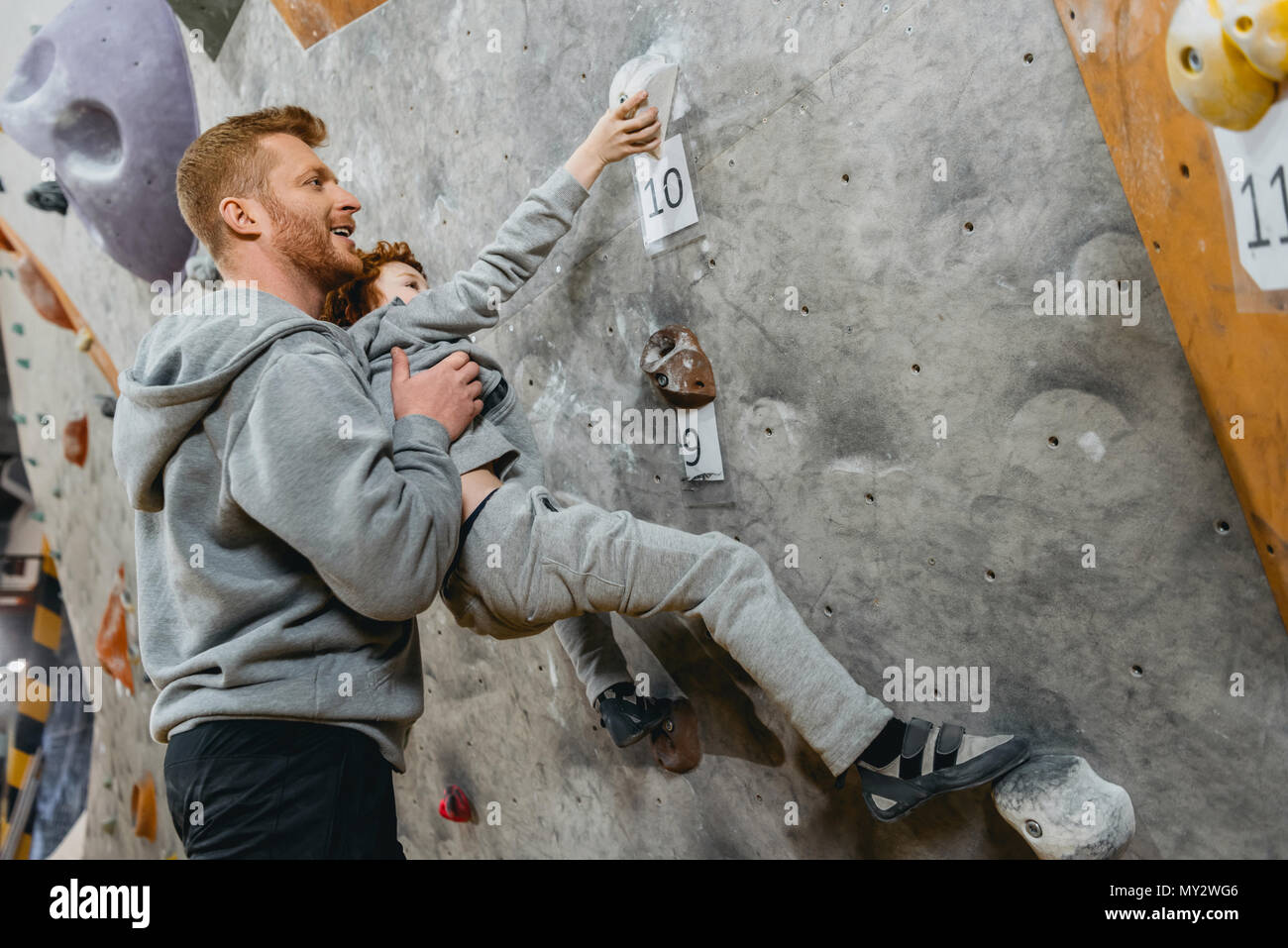 Young dad teaching his little son how to climb a wall with grips at gym - Stock Image