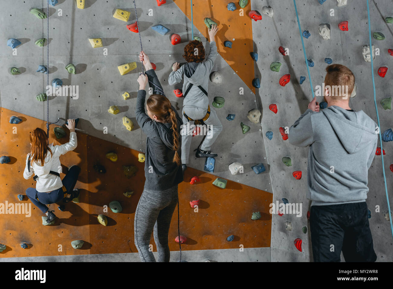 Two little kids climbing a wall at gym and their mother and father holding securing ropes - Stock Image
