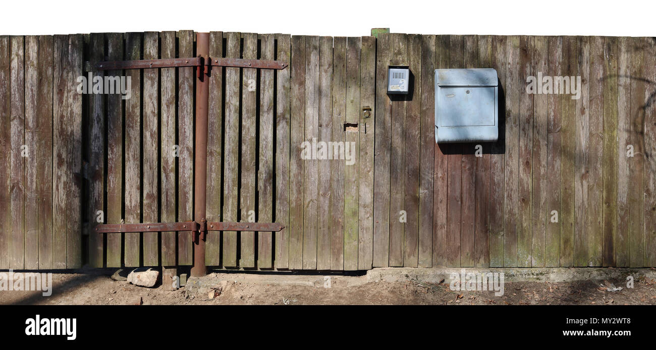 Crooked ugly wooden rural aged fence  with mail box isolated on top. Sunny spring day panoramic shot - Stock Image