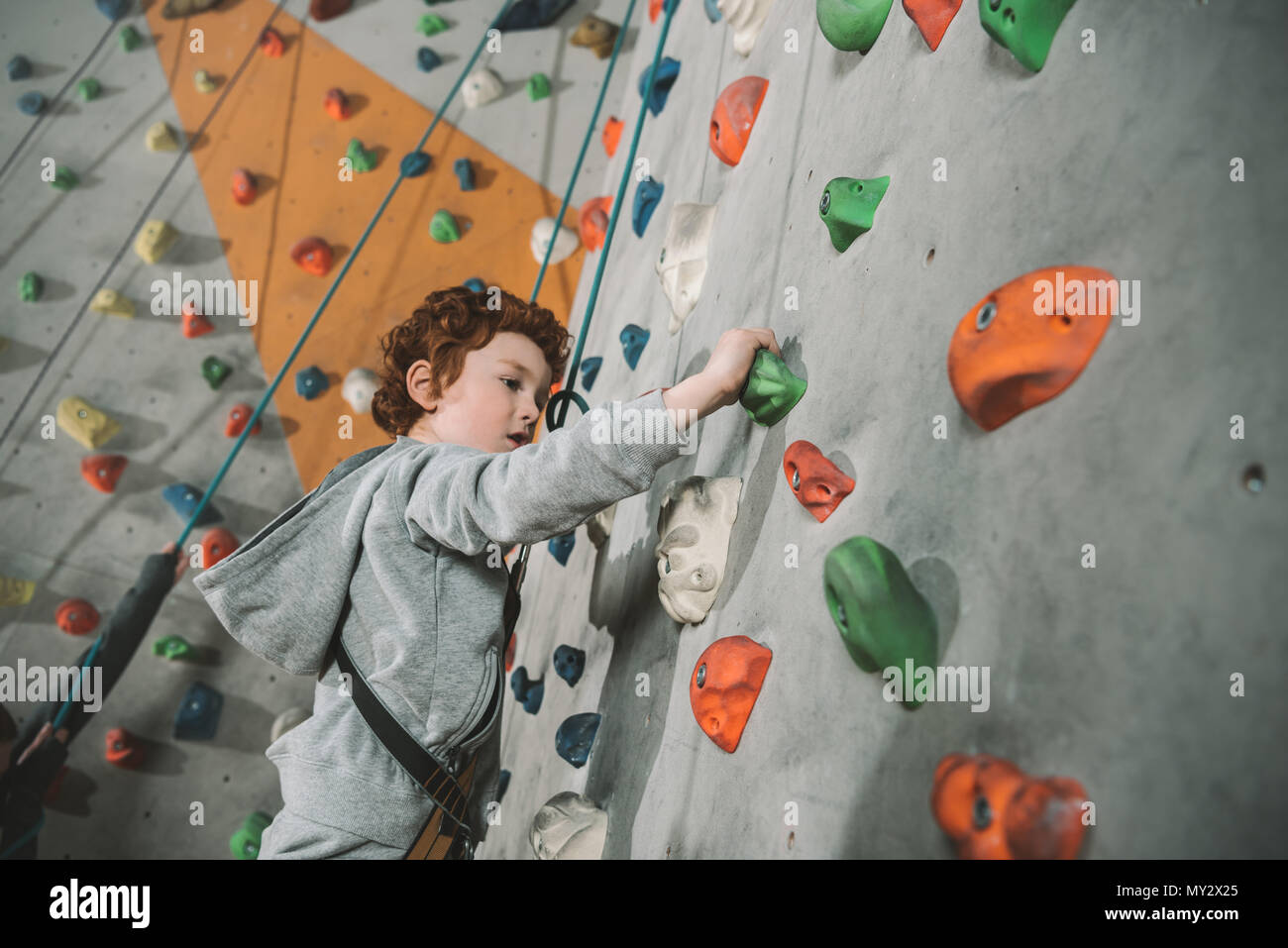 Half-length shot of little boy in a harness climbing a wall with grips at gym - Stock Image