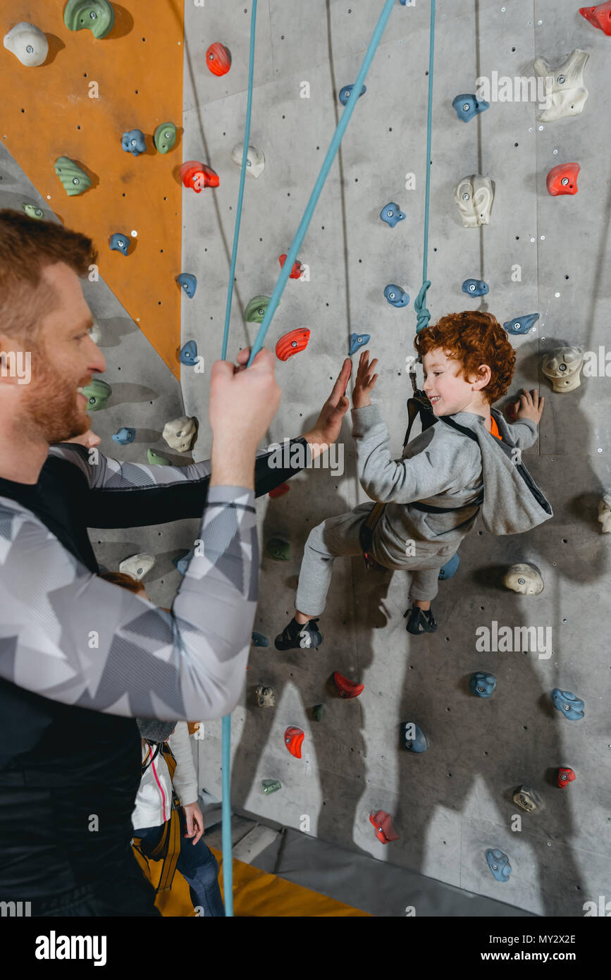 Little boy in harness hanging on a climbing wall and high-fiving father - Stock Image