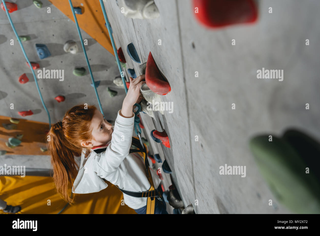 High angle shot of little girl in a harness climbing a wall with grips at gym - Stock Image