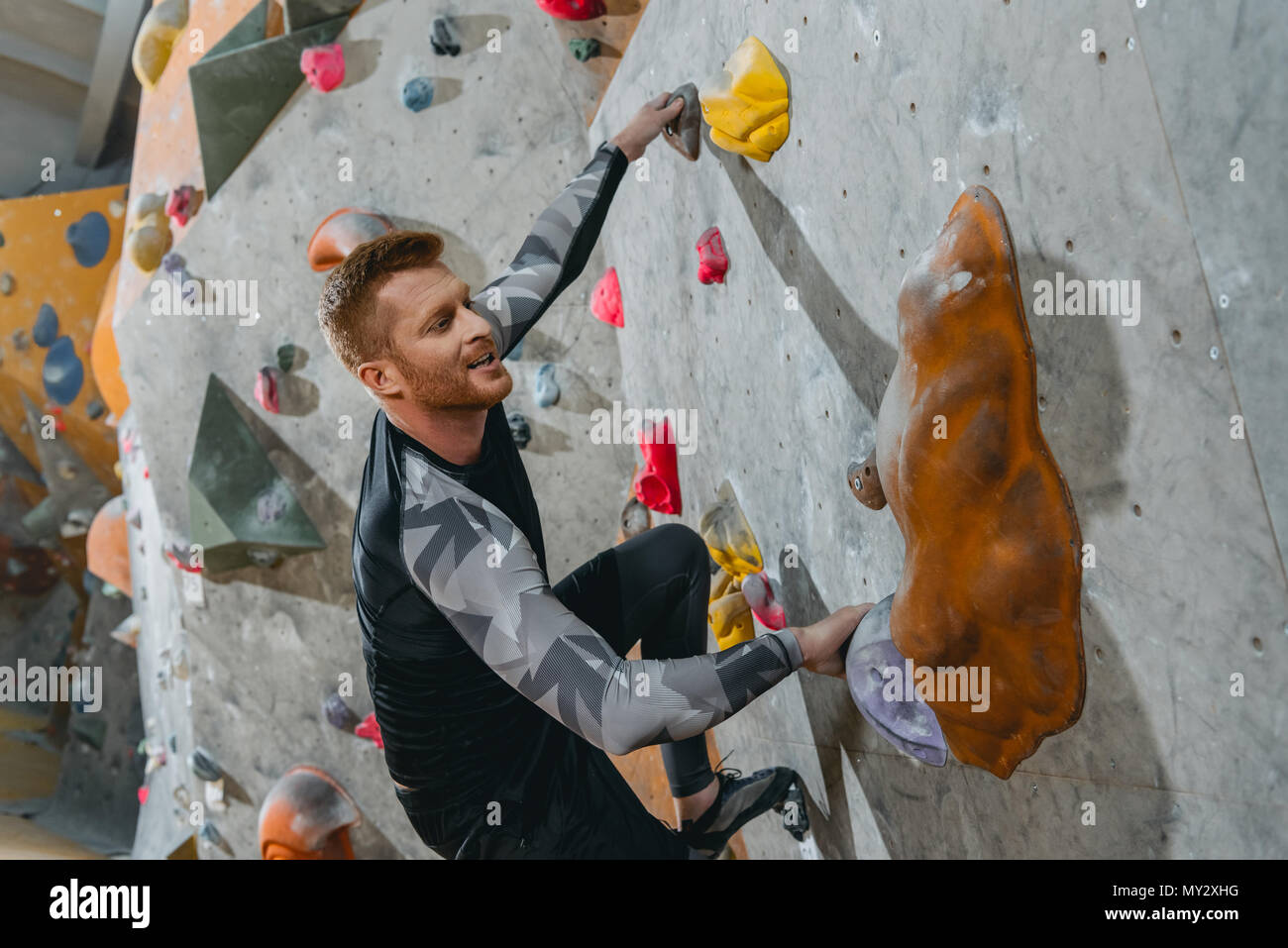 Young man in sportive attire climbing a wall with grips at gym - Stock Image