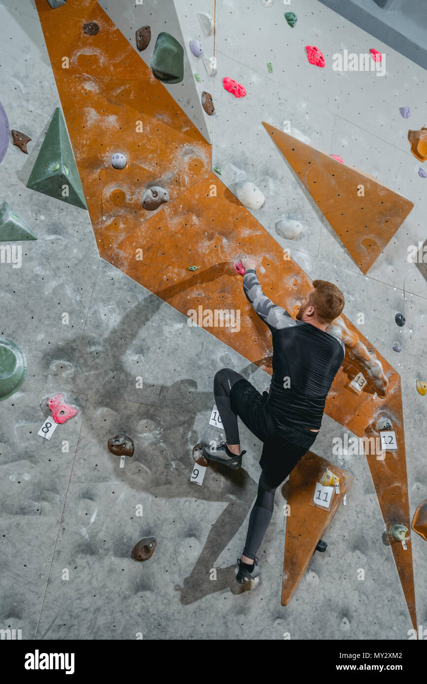 Full-length shot of young man in sportive attire climbing a wall with grips at gym - Stock Image