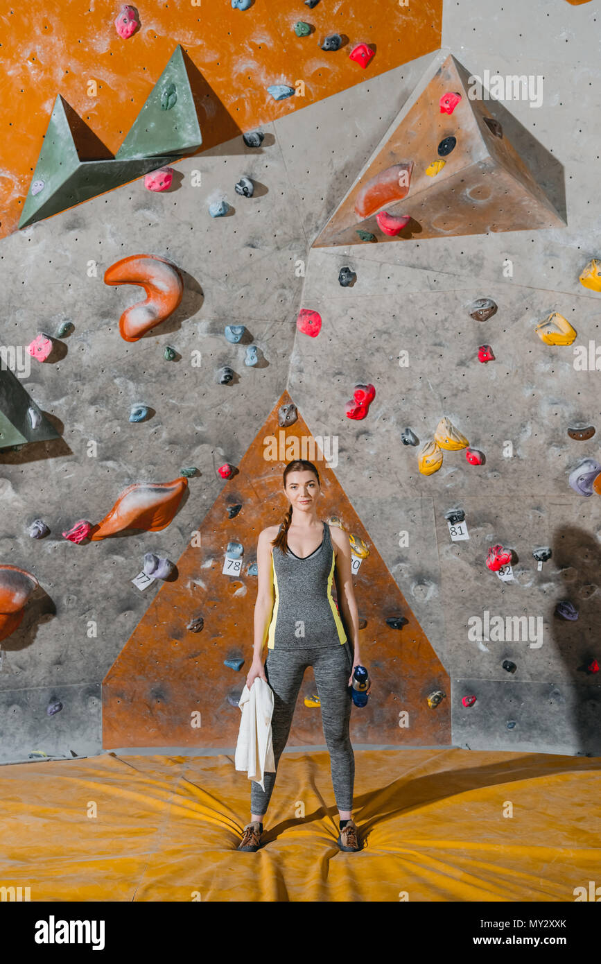 Full-length shot of a young woman in sportive attire posing in front of climbing wall - Stock Image