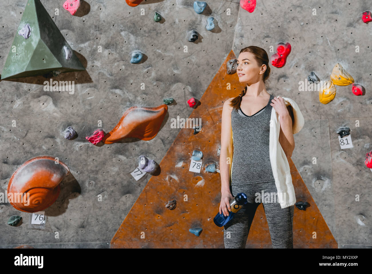 Half-length shot of a young woman in sportive attire posing in front of climbing wall - Stock Image