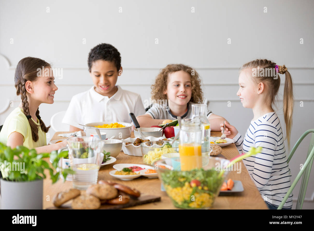 Smiling kids eating dinner while celebrating children's day at home - Stock Image