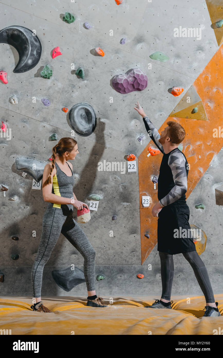 Full-length shot of young man pointing to grip on climbing wall and woman beside him looking at it - Stock Image