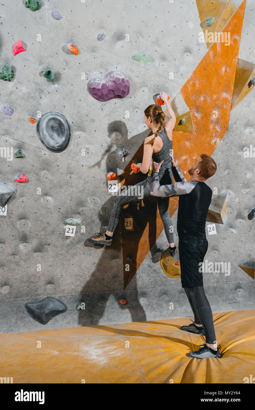 Full-length shot of young woman climbing a wall with grips with man supporting her from behind - Stock Image
