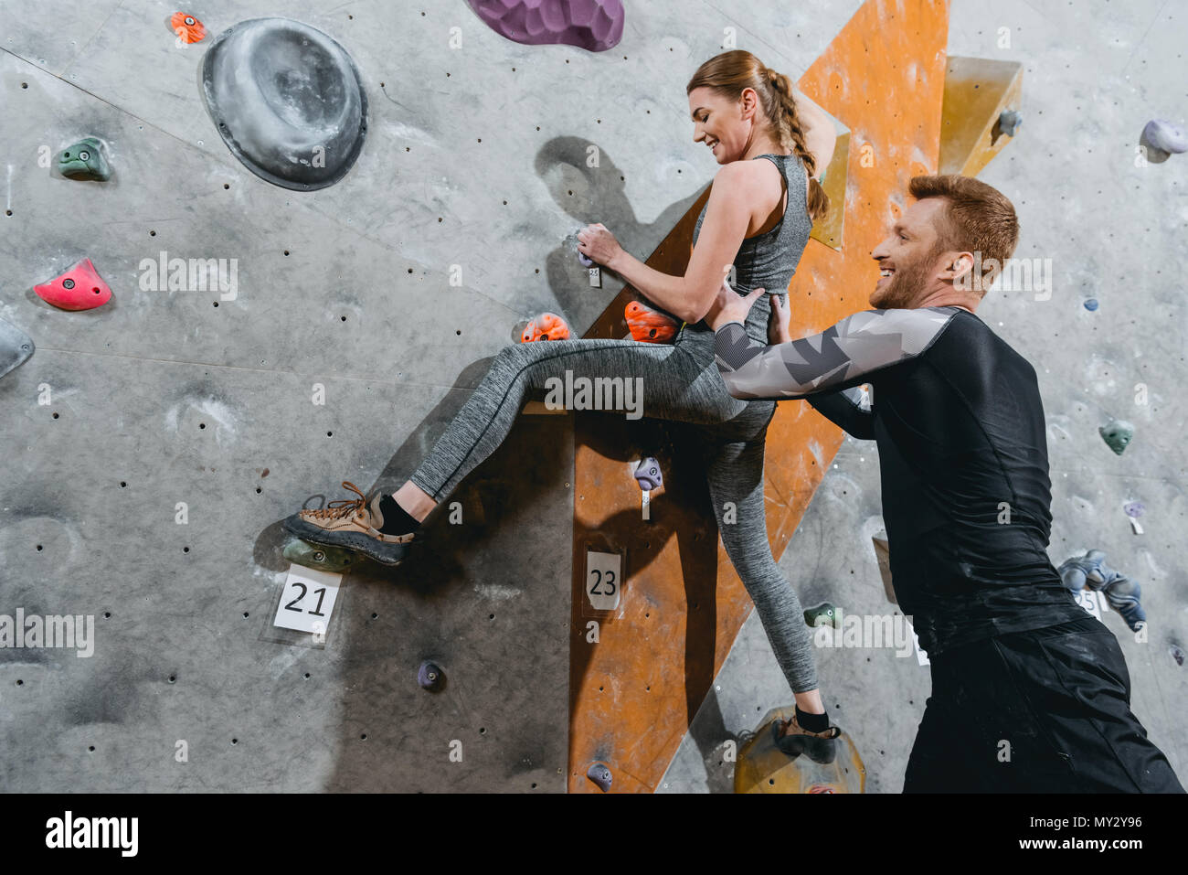 Young woman climbing a wall with grips with man supporting her from behind - Stock Image