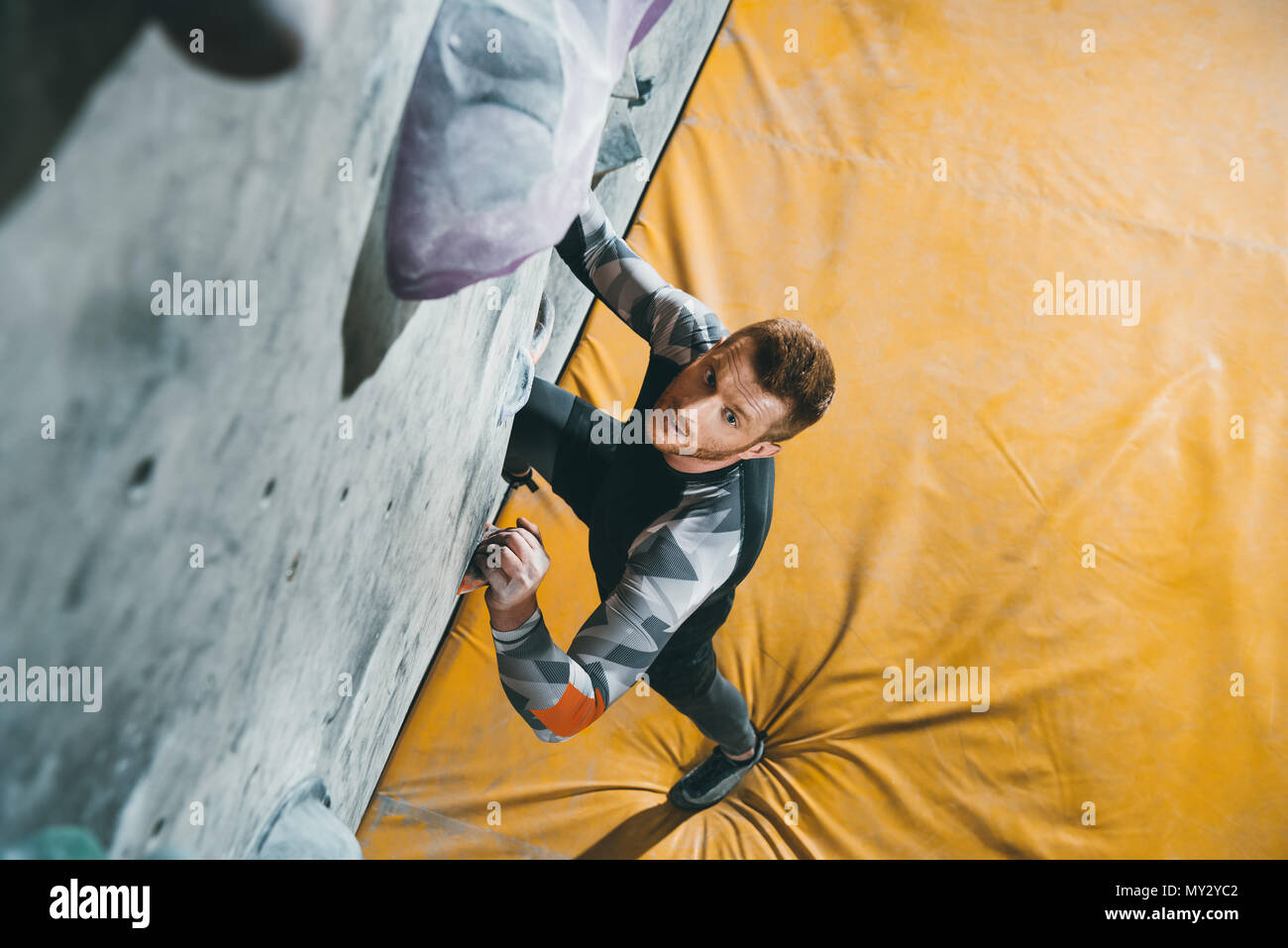 High-angle shot of young man in sportive attire climbing a wall with grips at gym - Stock Image