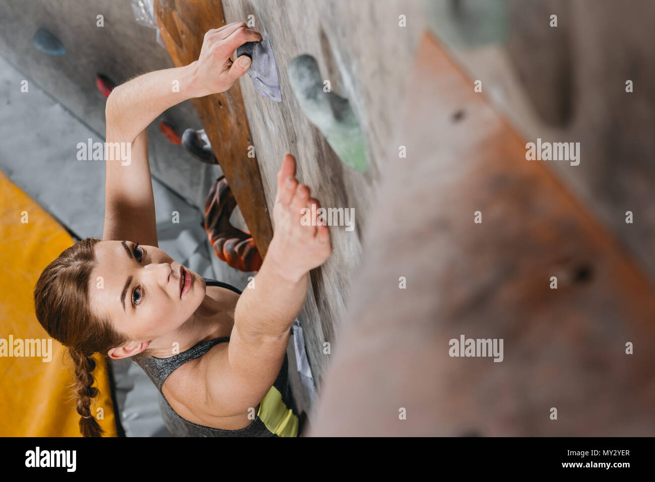 High-angle shot of young woman in sportive attire climbing a wall with grips at gym - Stock Image
