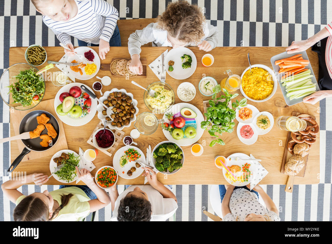 Top view on children eating healthy food during friend's birthday party - Stock Image