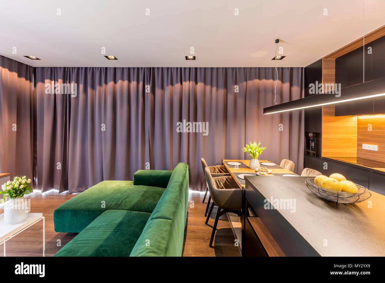 Green corner sofa in grey apartment interior with kitchen island