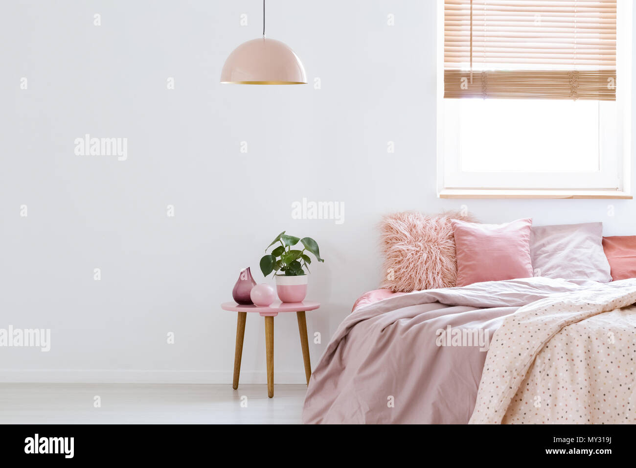 Cozy, feminine bedroom with pink bed, decorative cushions ...