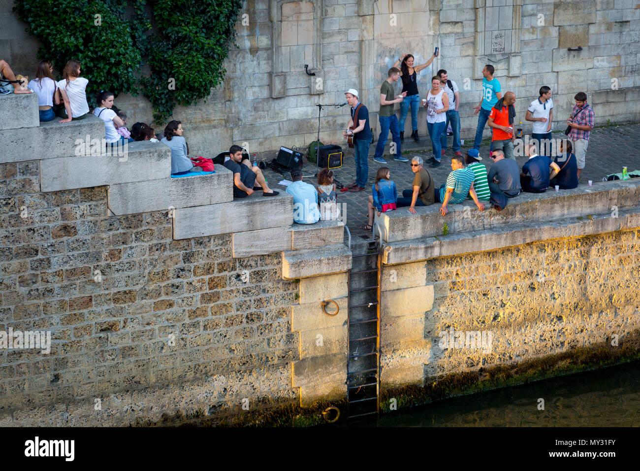 Parisians along River Seine celebrate Fête de la Musique - annual city-wide music festival each June 21st, Paris, France - Stock Image