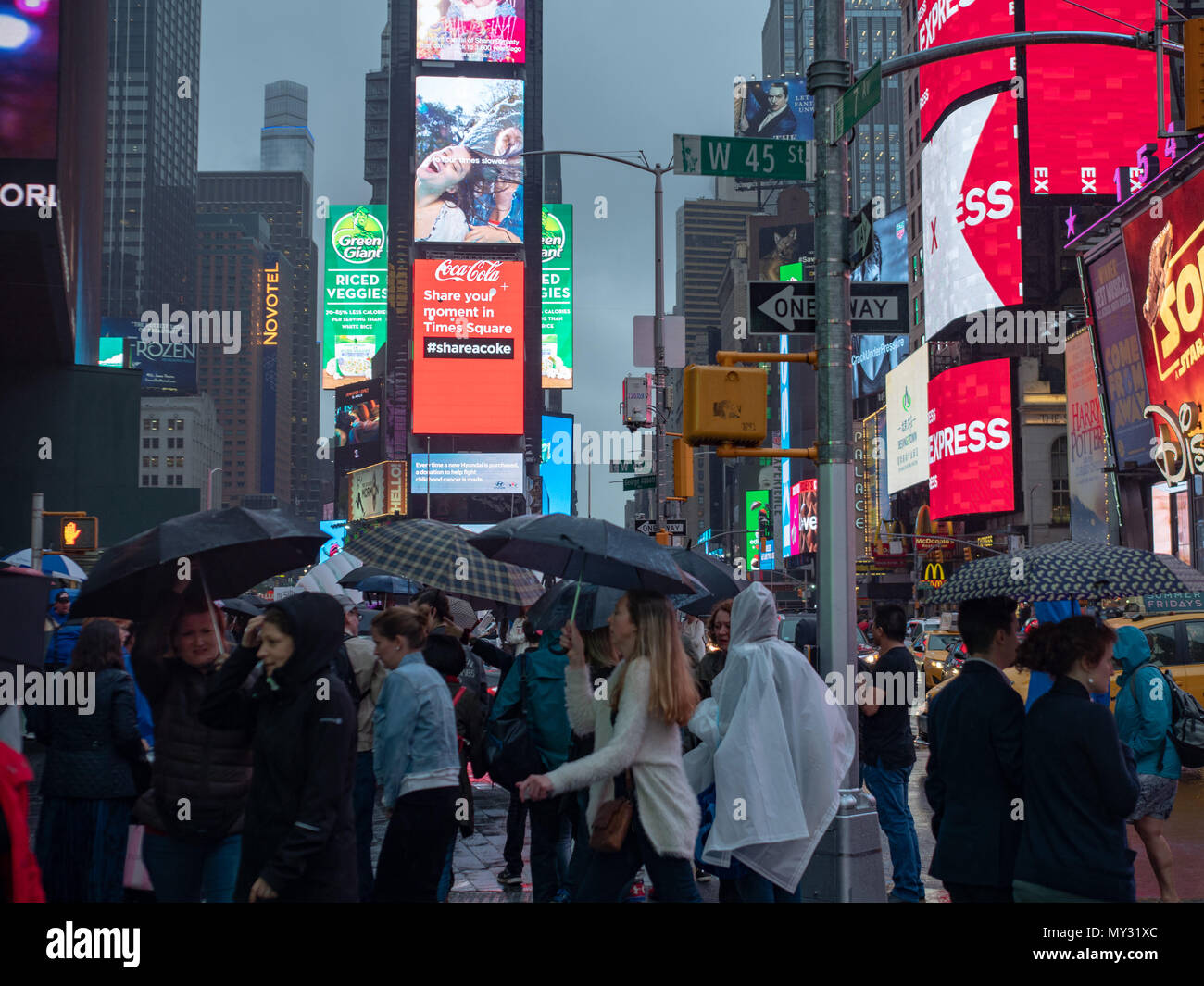 NEW YORK, NY – MAY 16, 2018: Tourists exploring Times Square while dodging rain - Stock Image