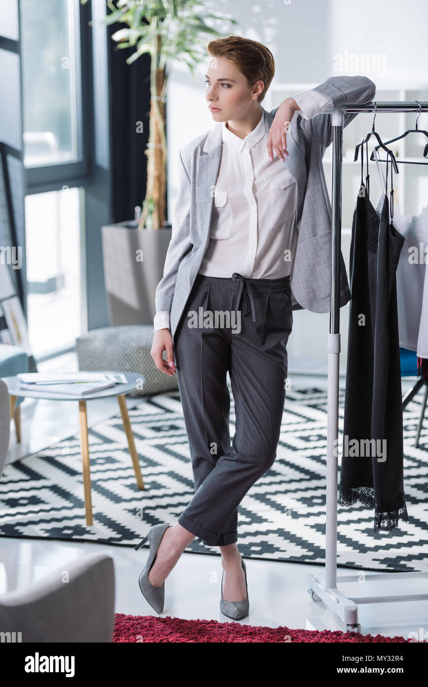 Beautiful Young Fashion Designer Leaning On Bar With Dresses And Looking Away Stock Photo Alamy