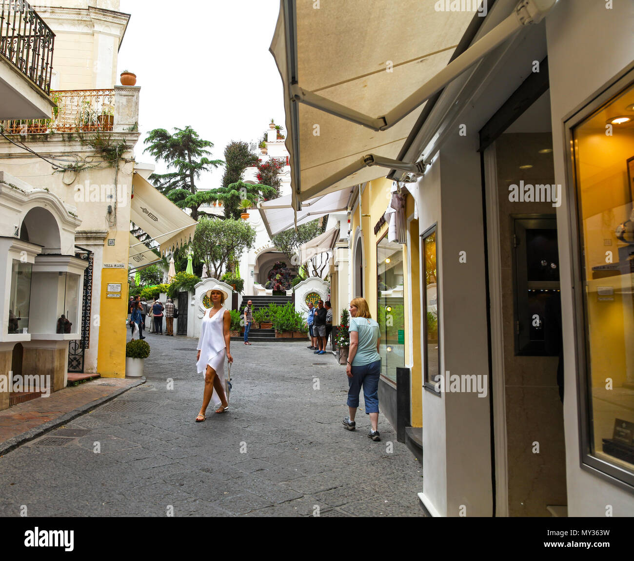 An elegant lady strolling the Via Camerelle, an expensive, up-market shopping street where they sell designer labels on the island of Capri, Italy - Stock Image
