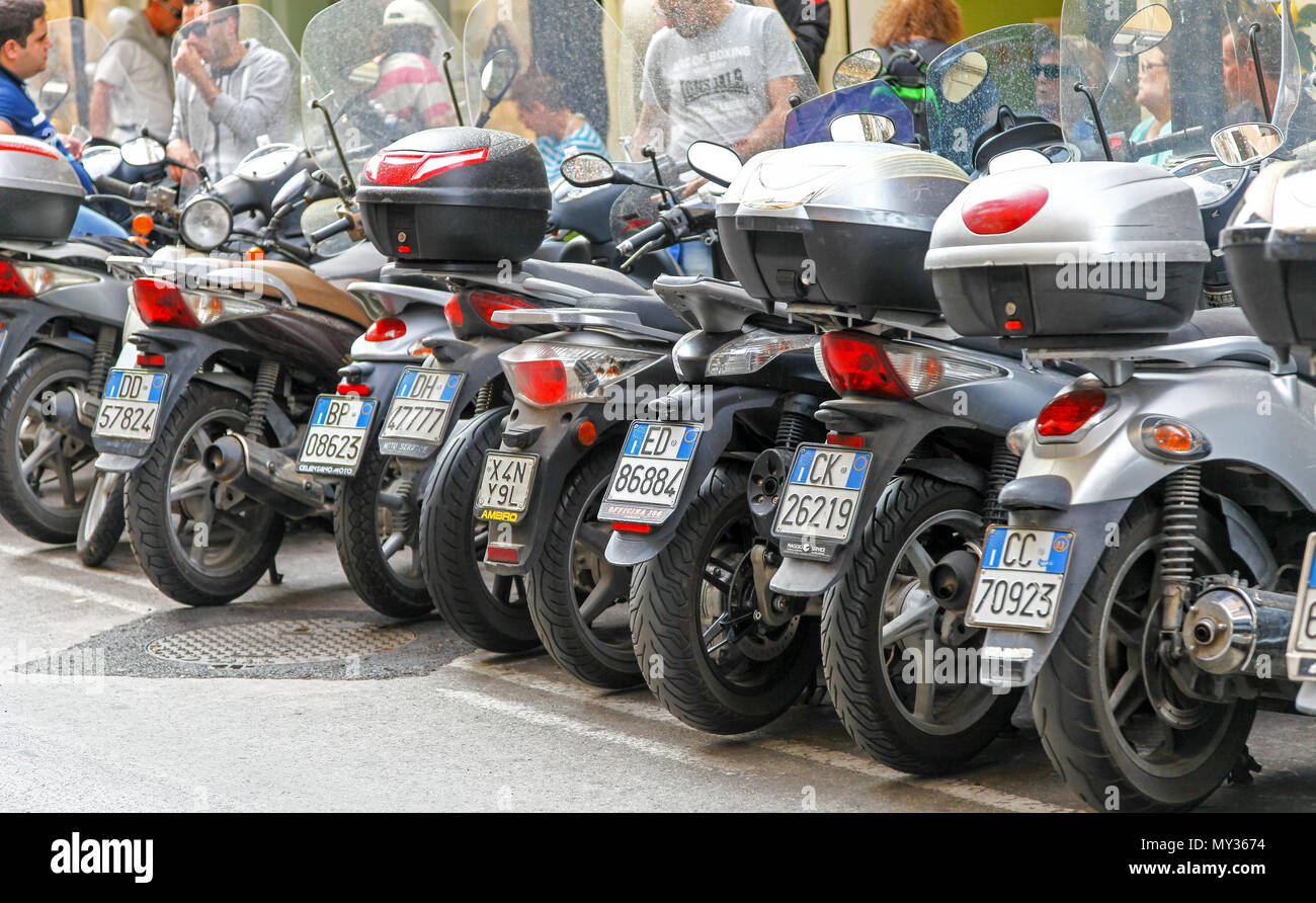 Motorbikes and motor scooters parked in a row in a street in Sorrento, Italy - Stock Image