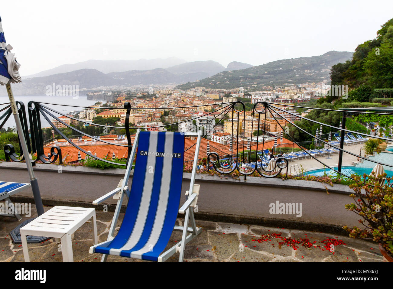 A blue and white striped deck chair with a view of the Bay of Naples in the background at the Grand Hotel Capodimonte, Sorrento, Italy - Stock Image
