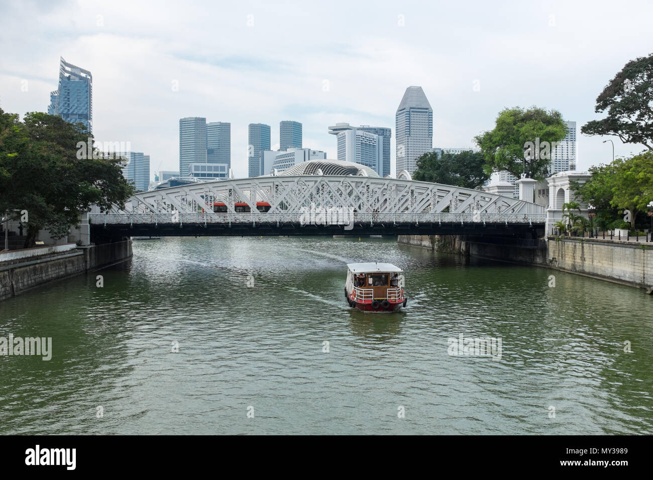 Tourists on Bumboat passing under Anderson Bridge on the Singapore River in Singapore - Stock Image