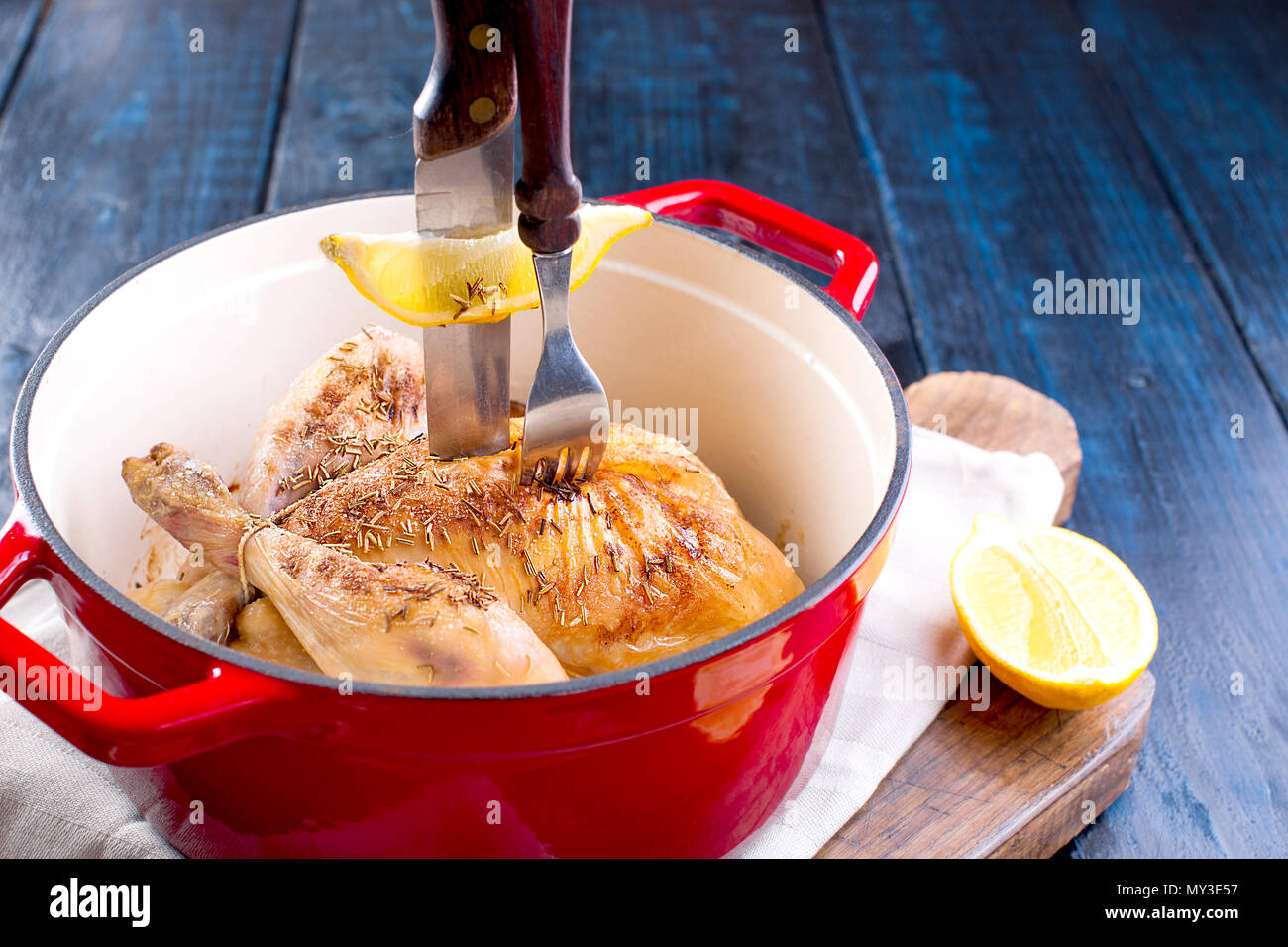 a cast-iron pot and a golden chicken with lemon and rosemary from the oven. Delicious family dinner. Place for text. copy space. Stock Photo