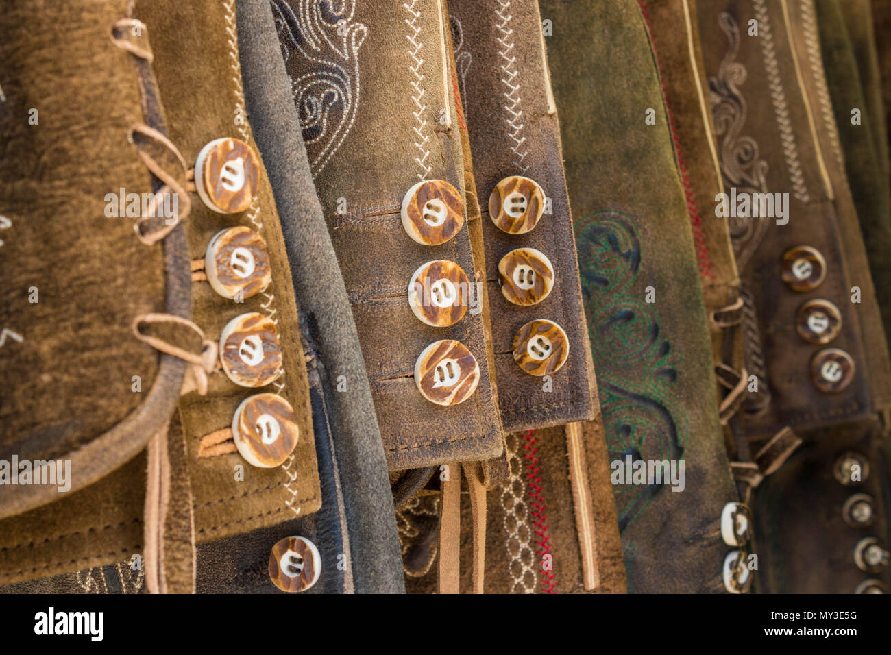 Traditional austrian and bavarian lederhosen (leather pants). Various lederhosen hanging in a row. Closeup of buttons. - Stock Image