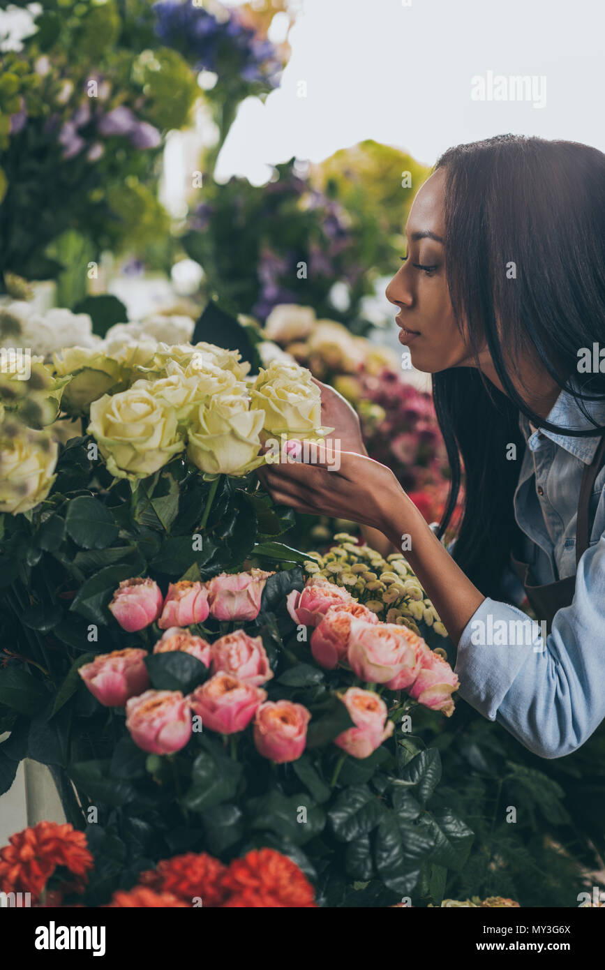 young african american woman smelling beautiful roses in flower shop - Stock Image