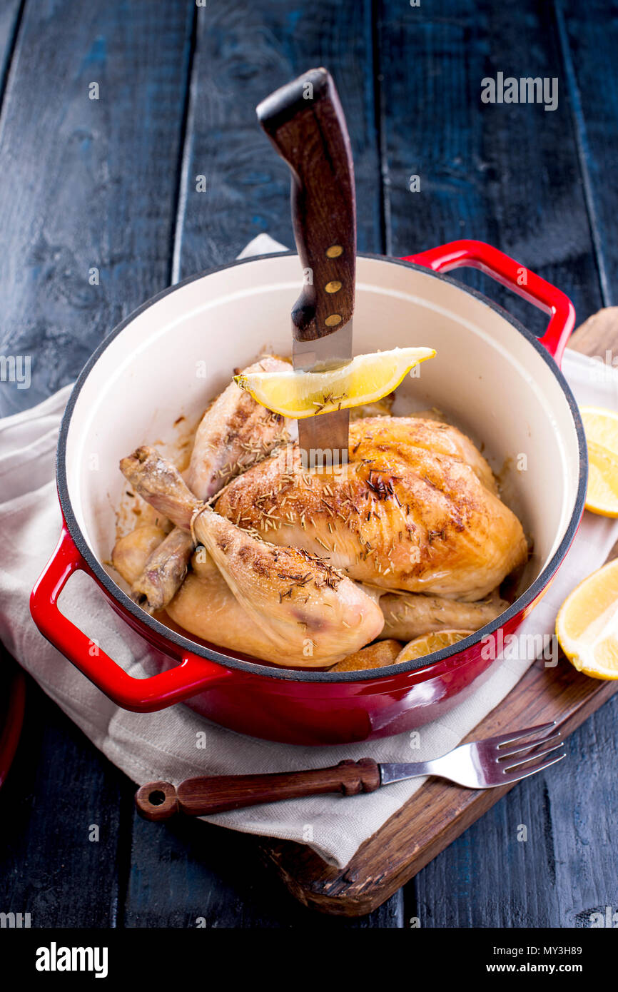 a cast-iron pot and a golden chicken with lemon and rosemary from the oven. Delicious family dinner. Place for text. copy space Stock Photo