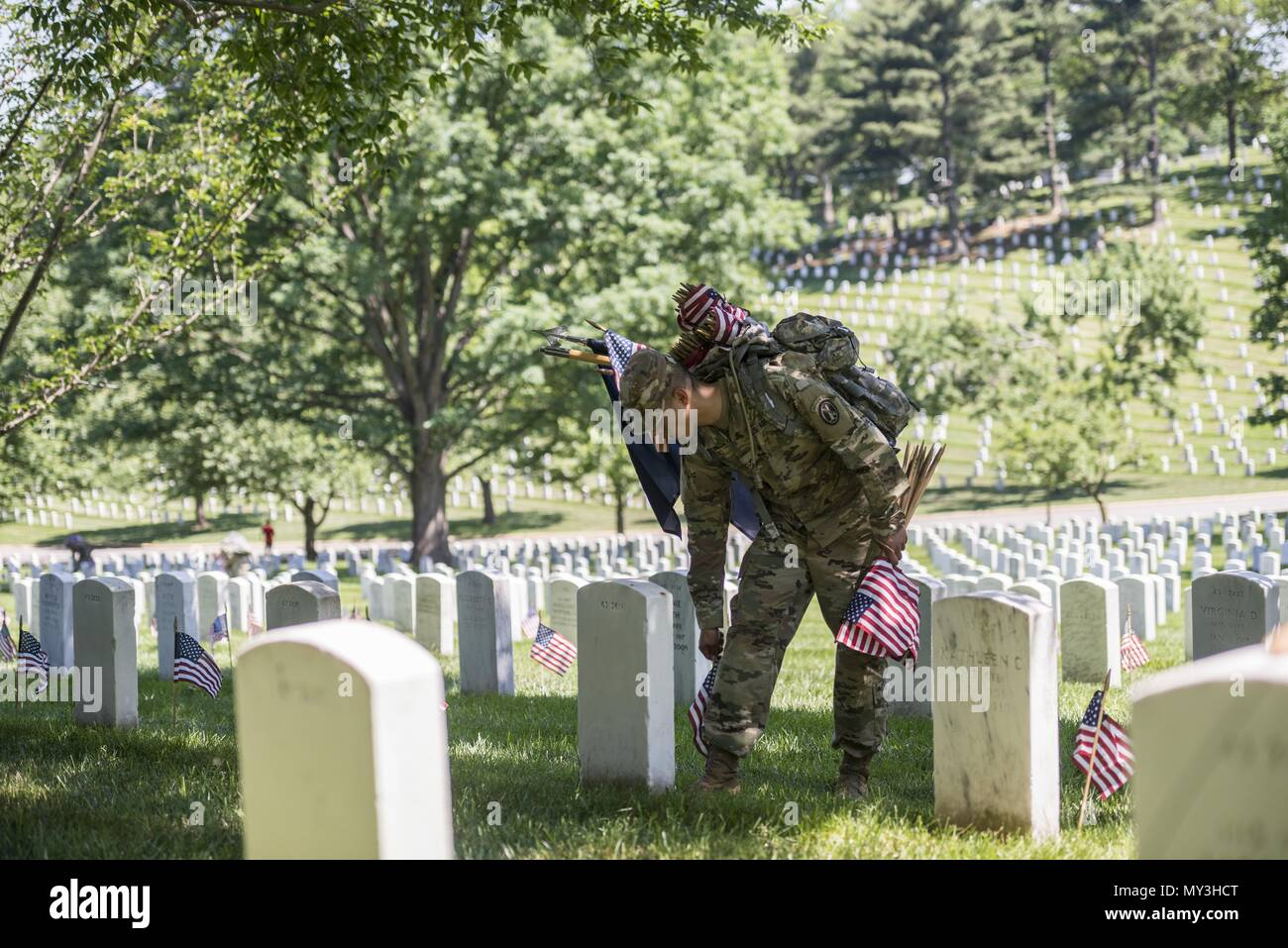 A Soldier from the 3d U.S. Infantry Regiment (The Old Guard) places U.S. flags at headstones in Section 43 during Flags In at Arlington National Cemetery, Arlington, Virginia, May 24, 2018, May 24, 2018. For more than 60 years, Soldiers from the Old Guard have honored our nation's fallen heroes by placing U.S. flags at gravesites for service members buried at both Arlington National Cemetery and the U.S. Soldiers' and Airmen's Home National Cemetery just prior to the Memorial Day weekend. Within four hours, more than 1, 000 Soldiers placed 234, 537 flags in front of every headstone and Columba - Stock Image