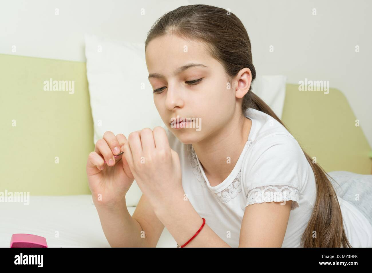 The girl is 10 years old at home on the bed in her home clothes, nails her nails using manicure accessories. - Stock Image