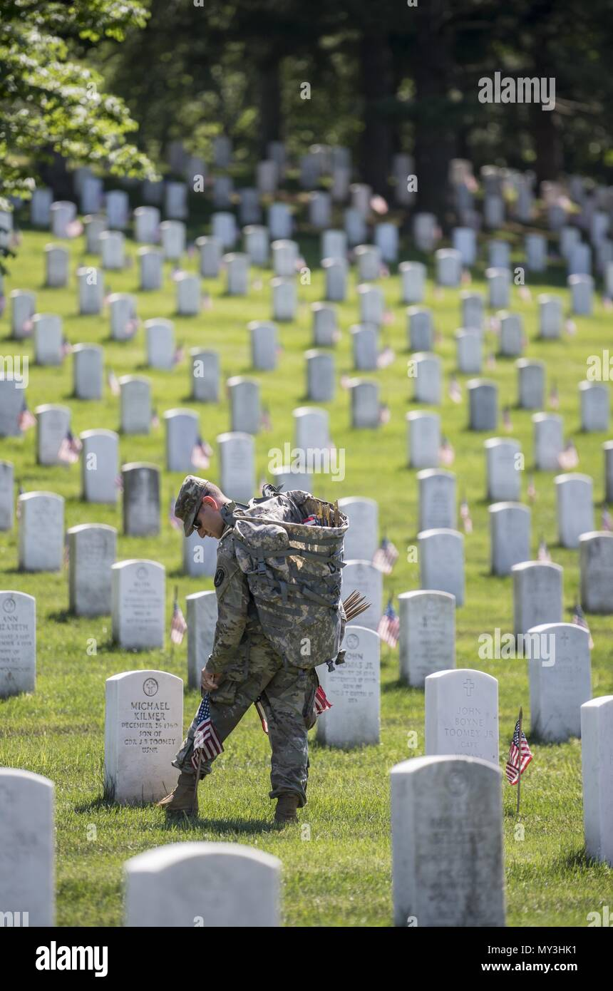 A Soldier from the 3d U.S. Infantry Regiment (The Old Guard) places U.S. flags at headstones in Section 38 during Flags In at Arlington National Cemetery, Arlington, Virginia, May 24, 2018, May 24, 2018. For more than 60 years, Soldiers from the Old Guard have honored our nation's fallen heroes by placing U.S. flags at gravesites for service members buried at both Arlington National Cemetery and the U.S. Soldiers' and Airmen's Home National Cemetery just prior to the Memorial Day weekend. Within four hours, more than 1, 000 Soldiers placed 234, 537 flags in front of every headstone and Columba Stock Photo