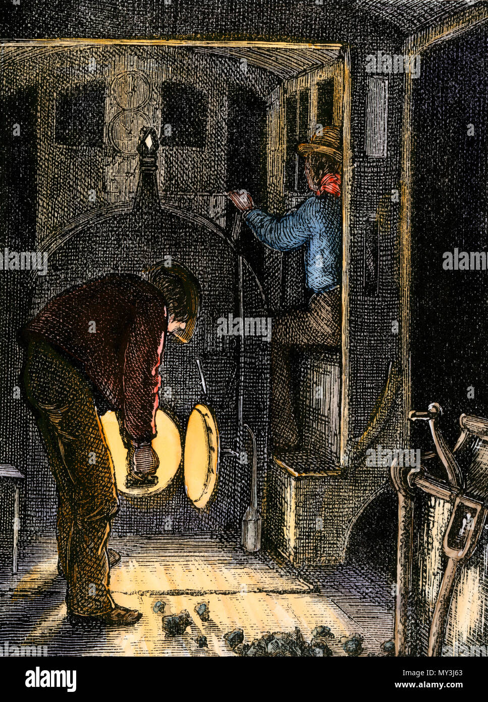 Shoveling coal in the cab of a steam locomotive at night, 1800s. Hand-colored woodcut - Stock Image