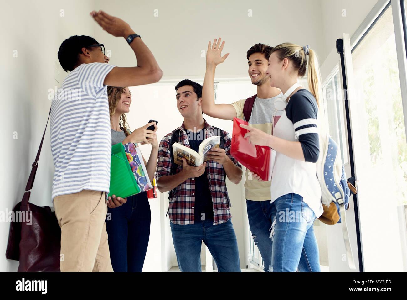 Teenage friend greeting stock photos teenage friend greeting stock students giving each other a high five in corridor stock image m4hsunfo