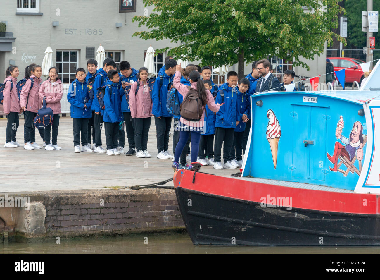 line of Chinese school kids waiting to buy ice cream in the UK - Stock Image