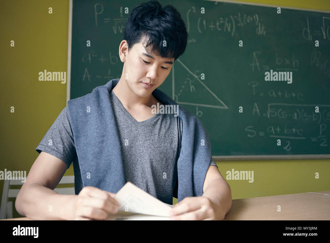 Young man studying in math class - Stock Image
