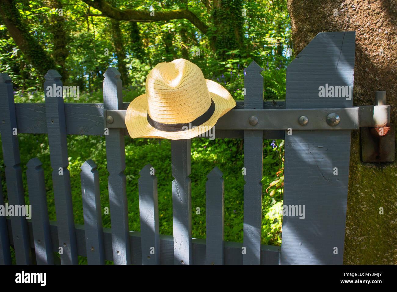 A mans straw hat left on a garden gate - John Gollop - Stock Image