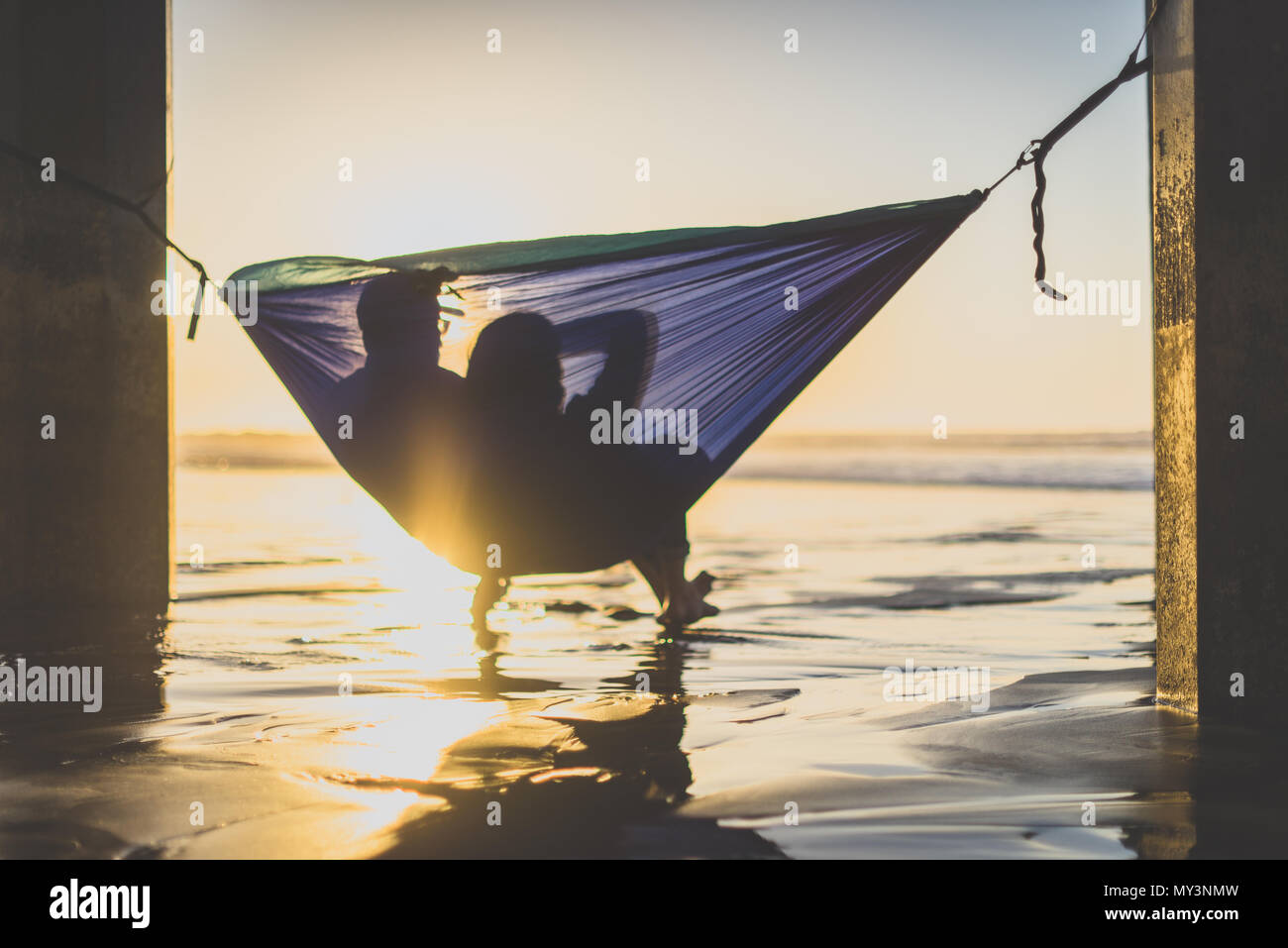 Silhouette of couple watching the sunset at the beach in a hammock - Stock Image
