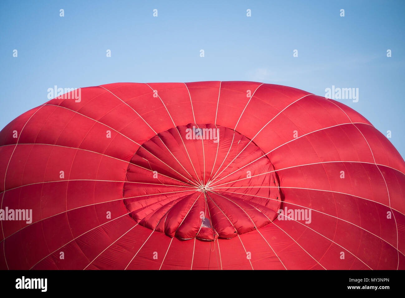 A hot air balloon canopy is slowly inflated prior to an evening ride above York. - Stock Image
