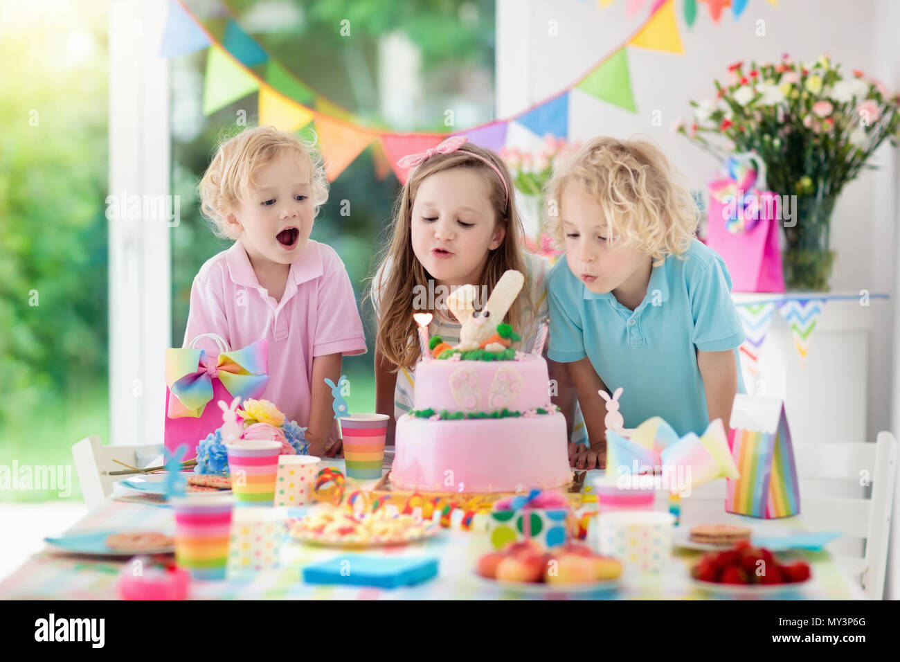 Kids Birthday Party Children Blow Out Candles On Pink Bunny Cake Pastel Rainbow Decoration And Table Setting For Event Banner Flag Girl A